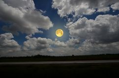 Full moon and white clouds over the field. Beautiful full moon and white clouds over the field and forest in the night Stock Photo