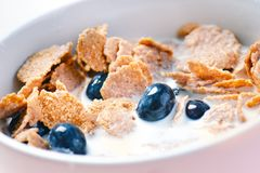 Full muesli bowl on a white table with blueberry and milk splash. Healthy breakfast cereals with milk, seed, fruit. Oat flakes. Full muesli bowl on a white table Royalty Free Stock Photo