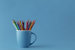 Full mug of sharp color pencils on monochromatic blue background Royalty Free Stock Photo