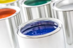 Full of multicolored paint cans on white table.  royalty free stock image