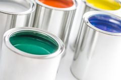 Full of multicolored paint cans on white table royalty free stock image