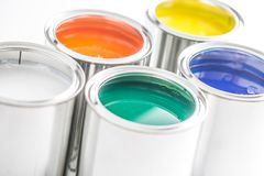 Full of multicolored paint cans on white table stock photo