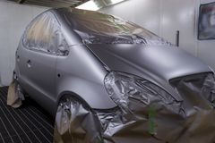 Full painting of a silver car in the back of a hatchback, some p. Arts of which are protected by paper from splashes of paint droplets in a car body repair shop stock images