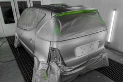 Full painting of a silver car in the back of a hatchback, some p. Arts of which are protected by paper from splashes of paint droplets in a car body repair shop stock photos
