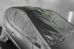 Full painting of a silver car in the back of a hatchback, some p. Arts of which are protected by paper from splashes of paint droplets in a car body repair shop royalty free stock photography