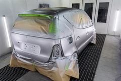 Full painting of a silver car in the back of a hatchback, some p. Arts of which are protected by paper from splashes of paint droplets in a car body repair shop royalty free stock photo
