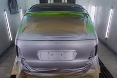 Full painting of a silver car in the back of a hatchback, some p. Arts of which are protected by paper from splashes of paint droplets in a car body repair shop royalty free stock image