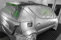 Full painting of a silver car in the back of a hatchback, some p. Arts of which are protected by paper from splashes of paint droplets in a car body repair shop stock photo