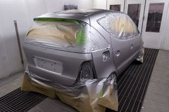 Full painting of a silver car in the back of a hatchback, some p. Arts of which are protected by paper from splashes of paint droplets in a car body repair shop stock image