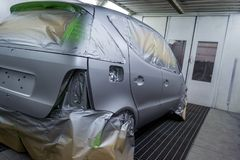 Full painting of a silver car in the back of a hatchback, some p. Arts of which are protected by paper from splashes of paint droplets in a car body repair shop royalty free stock photos