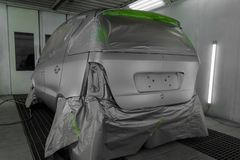 Full painting of a silver car in the back of a hatchback, some p. Arts of which are protected by paper from splashes of paint droplets in a car body repair shop stock photography