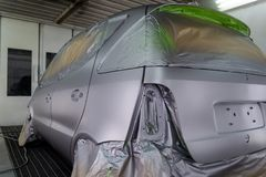 Full painting of a silver car in the body of a hatchback, some parts of which are protected by paper from splashes of paint. Droplets in a vehicle body repair stock photos