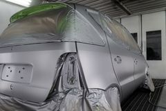 Full painting of a silver car in the body of a hatchback, some parts of which are protected by paper from splashes of paint. Droplets in a vehicle body repair royalty free stock photo