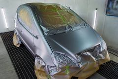 Full painting of a silver car in the body of a hatchback, some parts of which are protected by paper from splashes of paint. Droplets in a vehicle body repair royalty free stock images