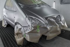 Full painting of a silver car in the body of a hatchback, some parts of which are protected by paper from splashes of paint. Droplets in a vehicle body repair stock images