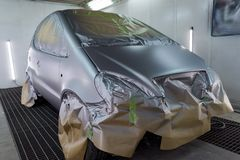 Full painting of a silver car in the body of a hatchback, some parts of which are protected by paper from splashes of paint. Droplets in a vehicle body repair royalty free stock photography
