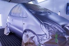 Full painting of a violet car in the body of a hatchback, some parts of which are protected by paper from splashes of paint. Droplets in a vehicle body repair stock image