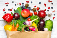 Full paper bag of different fruits, vegetables and berries on a white wooden background royalty free stock images