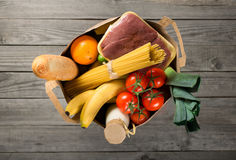 Full paper bag of different groceries on wooden background Stock Images