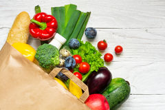Full paper bag of different health food on white wooden background. Top view. Flat lay stock photography