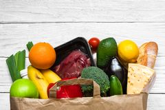 Full paper bag of different healthy food on white wooden background. fruits, vegetables and beef meat. Top view. Flat lay royalty free stock photos