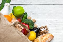Full paper bag of different healthy vegetarian food on white wooden background. fruits, vegetables, nuts, bread and milk Royalty Free Stock Image