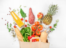 Full paper bag of healthy food on white background. Full paper bag of healthy food on a white background. Top view. Flat lay royalty free stock photos