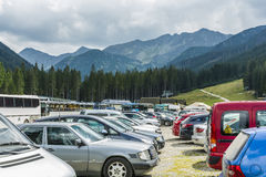 Full parking lot in the mountains. Zuberec, Slovakia - August  20, 2016: Cars and buses in the parking lot under the hood (Rohace - Spalena, Tatra west) of the Royalty Free Stock Photography
