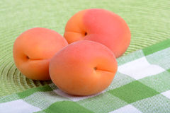 Full peaches close up on green material background. Stock Image