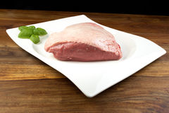 Full piece of raw cow beef picanha, with basil on a white dish Royalty Free Stock Photo