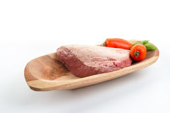 Full piece of raw cow beef picanha, tomatoes and basil on a wo Stock Images