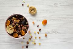 Full pink bowl of dried fruits and nuts on a white wooden background, top view. Overhead, from above, flat lay. Copy space.  royalty free stock photo