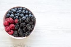 Full pink bowl of fresh berries: blackberry, raspberry, blueberry, view from above. Summer berry. Top view, overhead. Copy space Royalty Free Stock Image