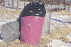 A full pink trash can waiting for pickup Stock Images