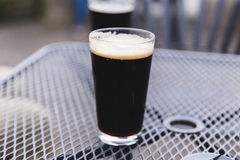 Full Pint Glass with Dark Beer. Pint glass full of a dark stout or porter beer. Outdoor patio setting stock photo