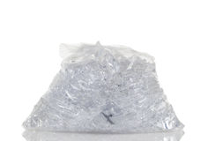 Full plastic bag of crushed ice isolated on white background wit. Plastic bag full of crushed ice cubes isolated on white with reflection stock images