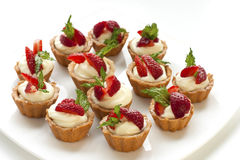 Full  plate of delicious fresh berries mini-cakes Stock Images