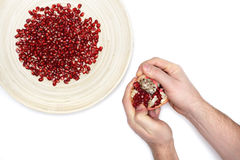 Full plate of peeled pomegranate seeds and a man de-seeding gran Stock Photo