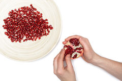 Full plate of peeled pomegranate seeds and a man de-seeding gran Stock Image