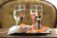 Full playful ornate champagne flutes. Horizontal shot of playful ornate champagne flutes for bride, groom and guests at wedding reception positioned on a tray Royalty Free Stock Image
