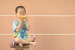 Full portrait of Asia boy in toddler age eating yellow corn Stock Photos