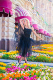 Full portrait of beautiful woman in black dress standing. In summer park around flowerpot with flowers Stock Images