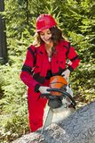 Full portrait of frail woman with a big chainsaw. Lumberjack in deep forest. royalty free stock photo