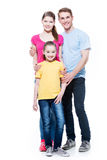 Full portrait of the happy young family. Full portrait of the happy young family with daughter in multicolor shirts - isolated on white background stock image