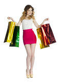 Full portrait of smiling young blonde girl with colorful shoppin Stock Photography