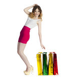 Full portrait of smiling young blonde girl with colorful shoppin Royalty Free Stock Photos