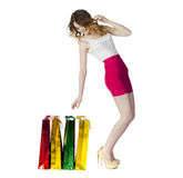 Full portrait of smiling young blonde girl with colorful shoppin Royalty Free Stock Image