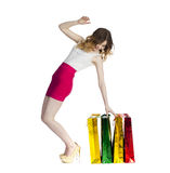 Full portrait of smiling young blonde girl with colorful shoppin Royalty Free Stock Images