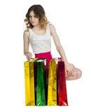 Full portrait of smiling young blonde girl with colorful shoppin Royalty Free Stock Photography