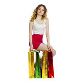 Full portrait of smiling young blonde girl with colorful shoppin Royalty Free Stock Photo